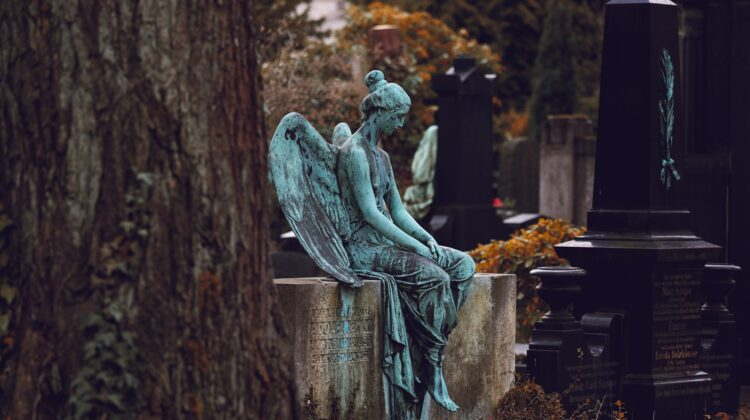 A statue of an angel with light teal patina sits atop a headstone in a cemetery, head downcast.