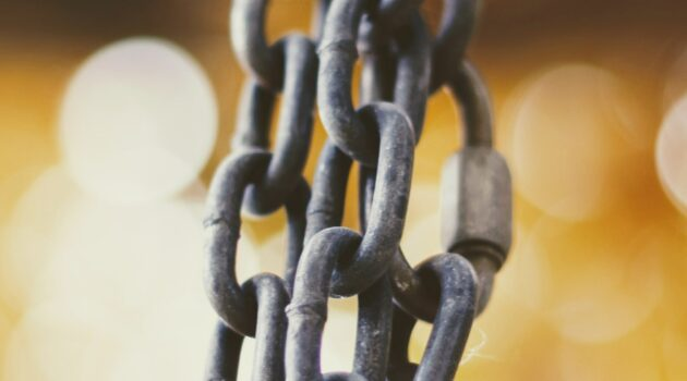 Layers of grey metal chain are in focus in the foreground, with bokeh of gold lights behind.