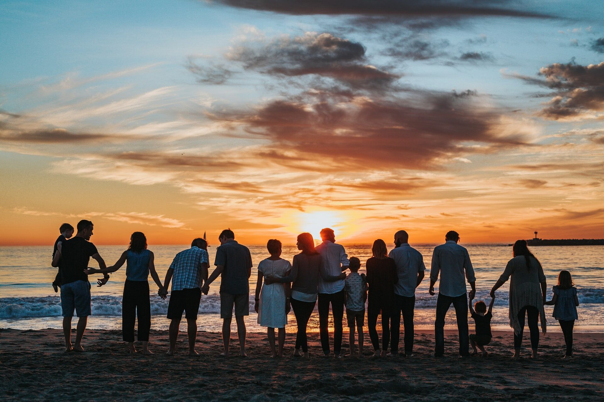 People stand together on a beach, facing the sunset behind the water.