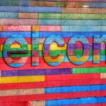 The word Welcome is writte from multicolored wooden boards, against a similarly colorful board background.